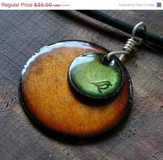 Linda Stanek's enamel on copper pendant necklace--a sweet little bird perched in Olive atop Mikado Orange. (Steinvika on etsy)