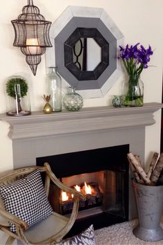 Here is a little mantle vignette we love. Simple. The starting point and center of attention is this amazing hexagon painted mirror from HomeGoods. We pulled out all our recycled glass pieces. Fresh flowers and a flickering candle complete the scene beautifully! Sponsored by HomeGoods