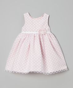 Simple and pretty, this frock flourishes under a classic print and sweet overlay on the skirt. A ruffled flower accent adds extra charm, while three buttons and a tie in back make sure it fits with ease.