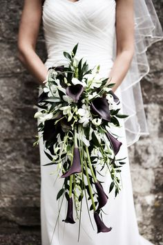 Such an elegant and modern long cascade bouquet of white dendrobium orchids, dark purple calla lilies, italian ruscus and bear grass.