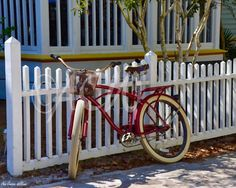 Red bicycle leaning on a white picket fence in Seaside Florida
