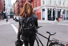MZ Wallace Co-Founder and Designer, Lucy Wallace Eustice, wearing the Black Bedford Cece Backpack as she heads out on Crosby Street on her Soho Trek Commuter bike. New York City.