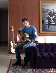 Adam Levine—of the band Maroon 5 and NBC's The Voice—with his vintage Gibson guitar in the living room of his Los Angeles home, which was decorated by Mark Haddawy.