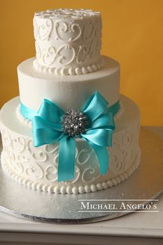 Teal Blue & Brooch #18Bow This three-tier cake is a popular design. Decorated with our signature swirls, it is accented with a teal colored ribbon and bow. The color ribbon can be changed to match the color of your wedding.