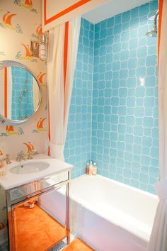 This very basic bathroom was made REALLY special with a colorful tub surround and a custom shower curtain , both in colors taken from the wallpaper. The mirrored vanity adds the illusion of space. Really well thought out.  Designer Bailey McCarthy Photography by Paige Newton