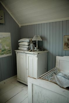 Vintage style child's room/nursery with wooden floor and wood panelling, in white and grey.