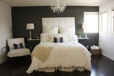 Dark grey accent wall, dark floors, white ceiling and moldings, crystal chandelier, white headboard and beddings, white night stands with big lamps, sheepskins on the floor, pink ruffled pillows on the bed and pink flowers on the night stands, black wooden shadows in the windows. Perfection.