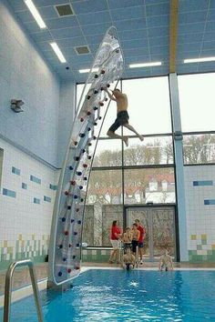 Indoor rock climbing wall above pool.