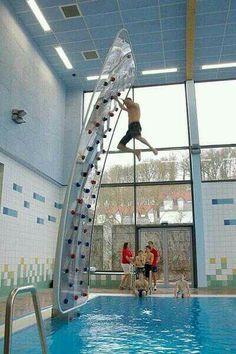 Indoor rock climbing wall above pool.