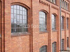 Schöne große alte Sprossenfenster einer alten Fabrik aus der Gründerzeit mit rotbrauner Fassade in Frankfurt-Fechenheim
