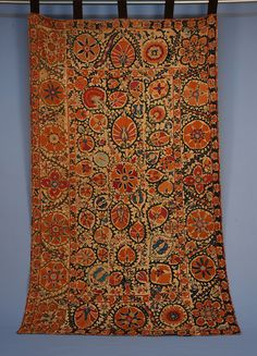 SUZANI, UZBEKISTAN, 19th C. Silk embroidery on cotton, five joined panels decorated in pumpkin, blue, purple and green silk with flowers and vinework, Ikat trim on verso, five velvet tabs attached for hanging. 53 x 90.