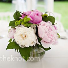 Fluffy light pink and dark pink peonies filled small, round vases on each table. Hadley was excited to use pastel colors for her French wedding since she had gone with an all-white color scheme for the American one.
