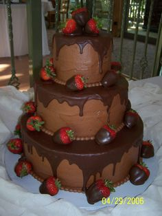 """3-tiered Chocolate Cake with Dipped Strawberries - Made this for a 50th wedding anniversary.  Triple Chocolate Fudge Cake with Chocolate Buttercream and that Betty Crocker Pour and Frost icing on top.  It's a 6""""-10""""14"""" - each tier is about 4 1/2 inches tall."""