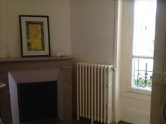 Marble fireplace and old cast iron radiator in bedroom of French house for sale in Limousin, France