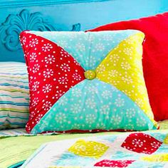 Four triangles make a merry, square pillow! Three bright prints form the hourglass block pillow. Complete it with a covered button center and piped edging.