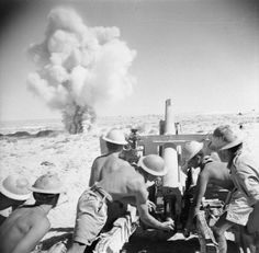 North Africa. British gunners hammer away at the enemy despite heavy counter fire which comes uncomfortably close.