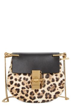 Swooning over this leopard print crossbody with gold hardware for a chic look. With its compact saddle-bag silhouette, squared-off flap and gilded chain strap, the mini Drew is a modern classic.