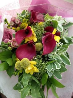 An absolutely gorgeous bouquet featuring 5 purple calla lilies, with stalks of yellow freesias, billy buttons, purple eustomas and wildflowers. For the cheerful girl who loves purple.