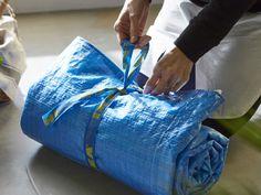 Gros plan d'une couverture de pique-nique roulée, réalisée avec des sacs bleus IKEA et des torchons de cuisine