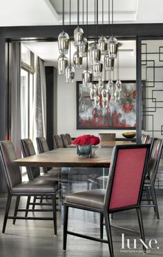 alison bergers light fixture from holly hunt suspends over two wood tables in this dining room bright special lighting honor dlm