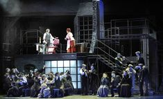 The lighting design for this scene of Sweeney Todd draws focus to the two characters on the platform by having high intensity light on them. The characters on the main stage are washed over with low intensity, blue light, which allows them to blend into the dull colored set. This makes me think that this lighting choice is a reflection of the meat pies that are made. These people are not considered to be individuals, but instead are just used as a means to make a profit.
