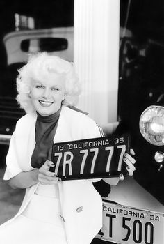 Jean Harlow holding her new California number plates, 1934. Photo by Margaret Chute