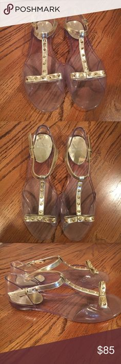 Stuart Weitzman clear rubber sandals with gold bow Stuart Weitzman clear rubber sandals with gold straps, studs, and bow. Adjustable closure. Worn, in good condition. Size 39 Stuart Weitzman Shoes Sandals