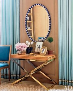 A very nice example of mixing different textures.  The oval mirror is an antique, and the X-base table is brass and rattan.