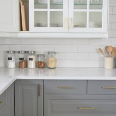 Putting the final touches on our kitchen - IKEA two toned cabinetry, quartz countertop, gold hardware, and classic white subway tile.