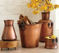 Copper cachepots with mustard-colored flowers against an off-white background with bits of black