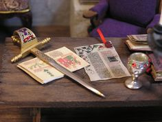 The King's Den ~ by T. Vanterpool ~ I made the book from a Roundtable kit, the sword, which has a rusty tip, is for hors d'oeuvres, I added finger nail jewels to both the sword and chalice. The excellent parchment was purchased for the room.