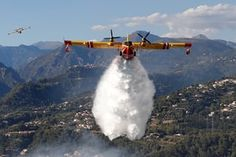 A plane drops water on a wildfire in a forest in Carros, near Nice
