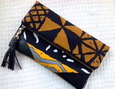 This Tribal Foldover Clutch is a beautiful blend of three prints. It has a a brown and black mud cloth design and a beautiful yellow, and sometimes