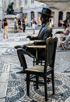 """Estátua de Fernando Pessoa, em Lisboa, diante do café que costumava frequentar.""""""""""""""""""""Pensar incomoda como andar à chuva Quando o vento cresce e parece que chove mais. Não tenho ambições nem desejos Ser poeta não é uma ambição minha É a minha maneira de estar sozinho.......É só porque sinto o que escrevo ao pôr do sol, Ou quando uma nuvem passa a mão por cima da luz E corre um silêncio pela erva fora.""""""""""""""""""""""""(Os 10 melhores poemas de Fernando Pessoa)"""