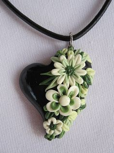 I created this black polymer clay heart with hand sculpted cream and green flowers and green leaves giving it a 3D effect.  I then coated it with a high gloss giving the flowers and leaves the look of porcelain.