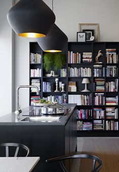 modern kitchen with library. black. like the lights --although not sure how much light they actually throw. Also love the library idea!