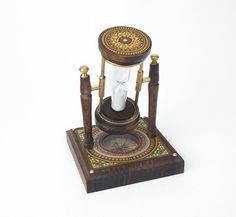 A charming combination piece. The rotating hourglass is mounted in wood and brass fixture on a wood base containing a compass. Beautifully decorated and runs for one minute - useful for timing to calc