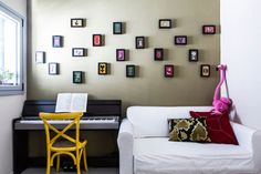 כרית מדוזה זהב בחדר אורחים בממ''ד, עם קיר שעוטר בגלויות שהוזמנו ברשת ומוסגרו. עיצוב ליאת עברון, צילום: איתי בנית