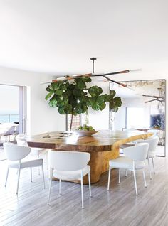A modern Phasmida chandelier by Christopher Boots contrasts a free-form, custom acacia-wood dining table designed by JAMIE BUSH + CO. and structural Minotti Mills dining chairs. An antique mirror creates the illusion of another window.