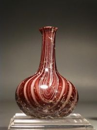 Early Roman red and white glass ribbon flask. 1st century AD.  H. 7.7 cm. (3 in.).  Repaired clean break at rim, otherwise perfect.