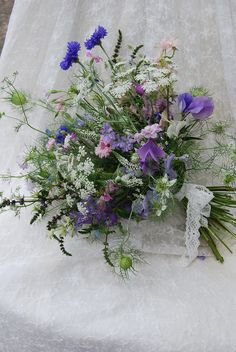 The bouquet on the left is a beautifully scented bridal bouquet including blue, white and the seed heads of Nigella, blue, pink and lilac cornflowers, Ammi, coriander flowers, flowering mint, lilac and white sweet peas, larkspur, veronica and a few other pretties