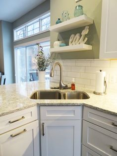 This gorgeous kitchen is made up of: Wellborn Forest Cabinetry: Door Style Chiswick Painted Confection (white) Cambria Countertops: in Berwyn Backsplash Tile: Hamption Neri 4x12 and trim 1x6 Hardware: by Top Knobs