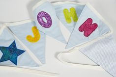 Personalised bunting with colourful letters on pink or baby blue flags. It is the ideal gift for a baby shower, Christening, Baptism or birthday.