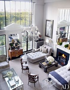 In the living room, a former artist's studio, the home's original circa-1908 chandelier hangs above a pair of Langham & Co. chaise lounges | archdigest.com