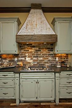 distressed cabinets with brick backsplash