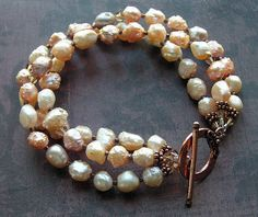 three strands of gorgeous RARE rosebud drusy freshwater baroque pearls in hues of natural colors such as pink, peach, ivory, golden-bronze, and silver-plum, spaced by tiny twinkling faceted seed beads and hand-cut crystals, and bali copper spacers    copper toggle    length ~ 8in