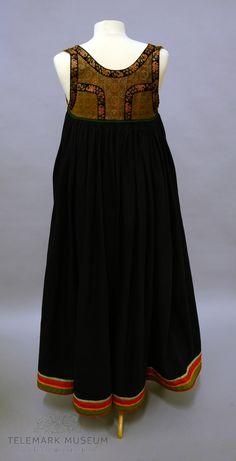 Stakken er av mørkeblått klede med åpning foran som lukkes med hekter, rundt linningen er det en grønn smal kant. Skoningen er på 6,5 cm, med rødt, grønt og orange bånd som dekor. Innsiden av skoningen er det grønt ulltøy. Livstykket er av brunt silkebrokade med silkebånd rundt ermutringningene og bak. Fòret er av ensfaget lintøy. Livet har 6 stk maljer på hver side av åpningen. Folklore, Ethnic, Museum, Costumes, Band, How To Wear, Inspiration, Clothes, Outfit