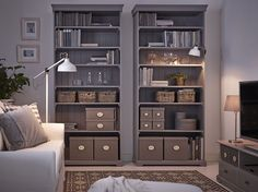 A living room with two grey bookcases filled with baskets and boxes in different sizes