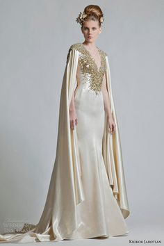 metallic sheath gown with cape style sleeves featuring neckline and back decorated with a burst of gold sequins