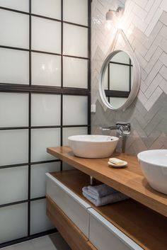 Herringbone subway tiles, white gray zig-zag, in a bathroom with a modern wood vanity and vessel sinks.